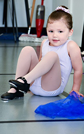 young girl sitting on floor in dance class